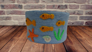 Knitted basket in a marine style with fish
