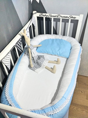 blue baby nest bed with white lace and pillow