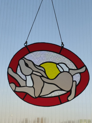 Stained glass windows. White-tailed bunny in an easter egg. Glass tiffany sunscreen.Stained glass suncatcher.